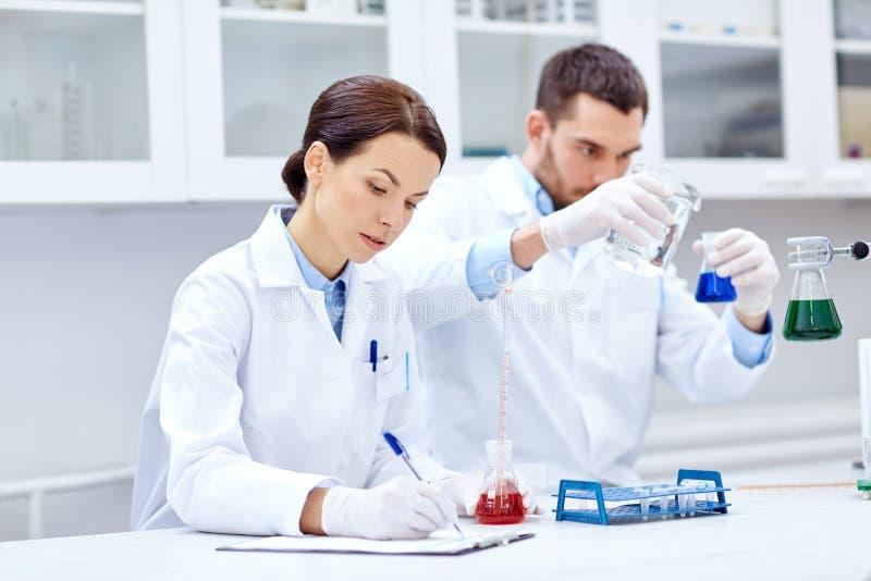 Молодые ученые делая испытание или исследование в лаборатории стоковое фото