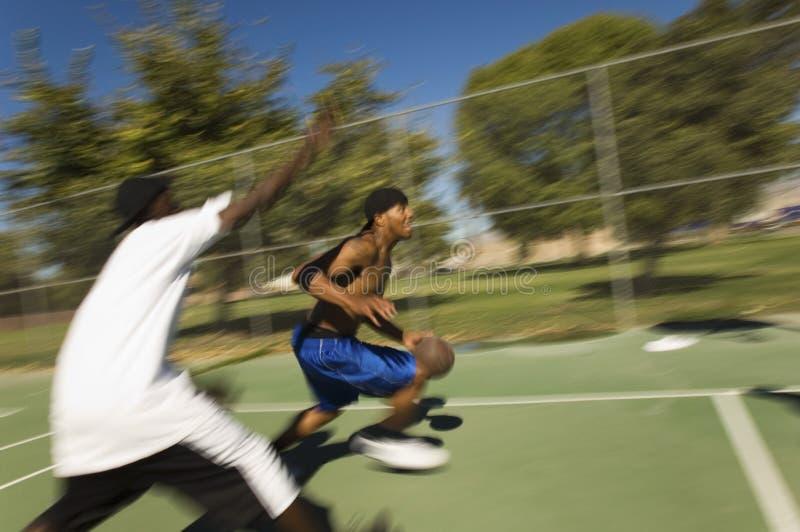 Молодые человеки играя баскетбол стоковое изображение rf