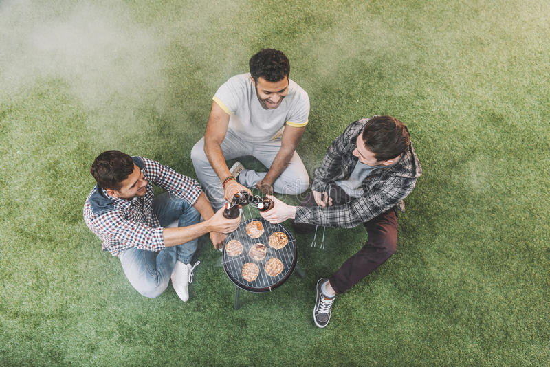 Молодые человеки сидя на траве и выпивая пиве пока жарящ мясо стоковая фотография