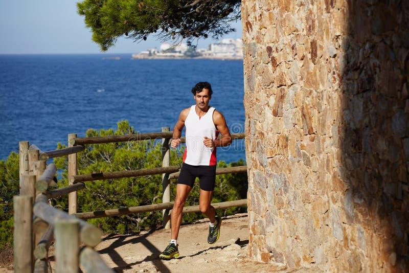Молодые человеки тратят время outdoors для jog вдоль сценарной холмистой области около океана Поезда профессиональные спортсмена  стоковое фото rf