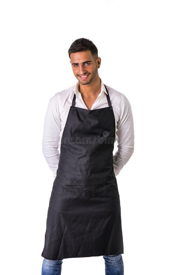 Молодые шеф-повар или кельнер нося черную изолированную рисберму стоковые изображения