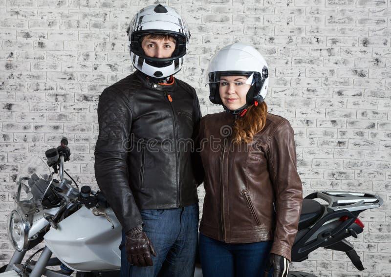Молодые любящие пары в обмундировании и шлемах мотоцикла стоя совместно около мотоцилк улицы в гараже стоковые изображения