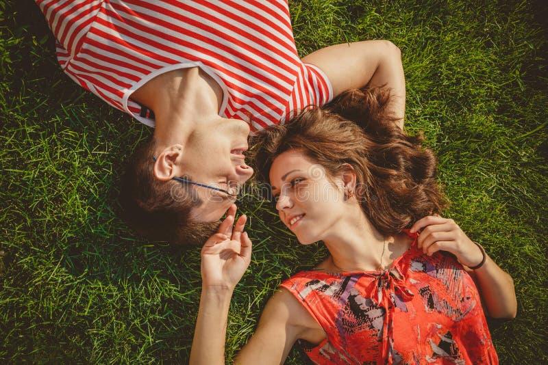 Молодые любящие пары лежащ совместно на равных на траве на лете Пикник семьи Оба в красных одеждах и руках держать Overhe стоковое изображение