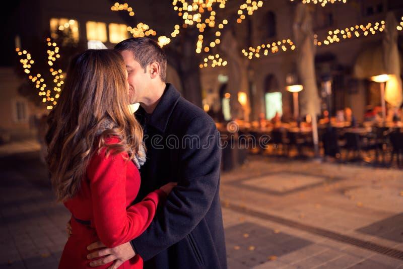 Молодые любящие пары целуя в центре города стоковое фото rf
