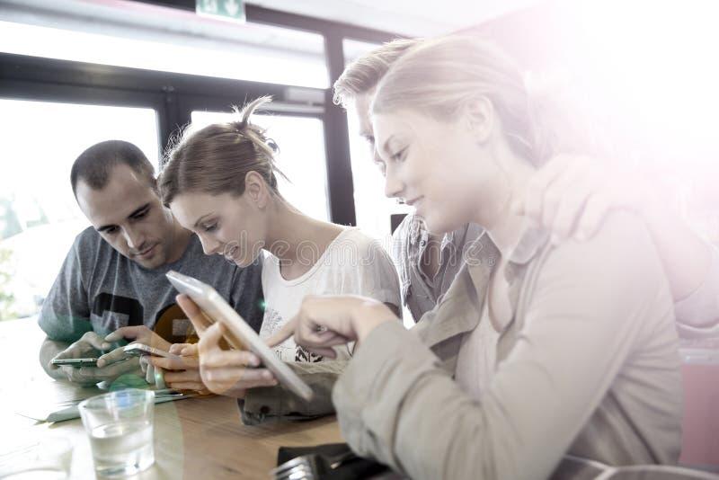 Молодые люди в снэк-бар подключенном на wifi стоковое изображение