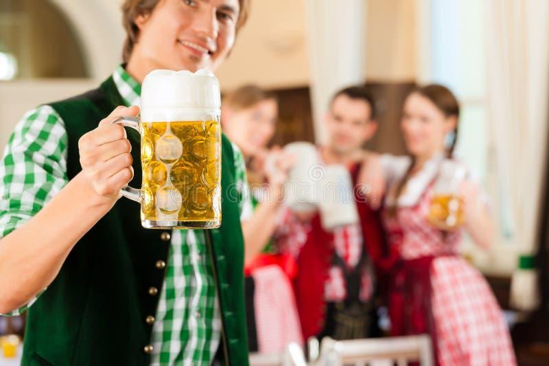 Молодые люди в традиционном баварском Tracht в ресторане или пабе стоковая фотография