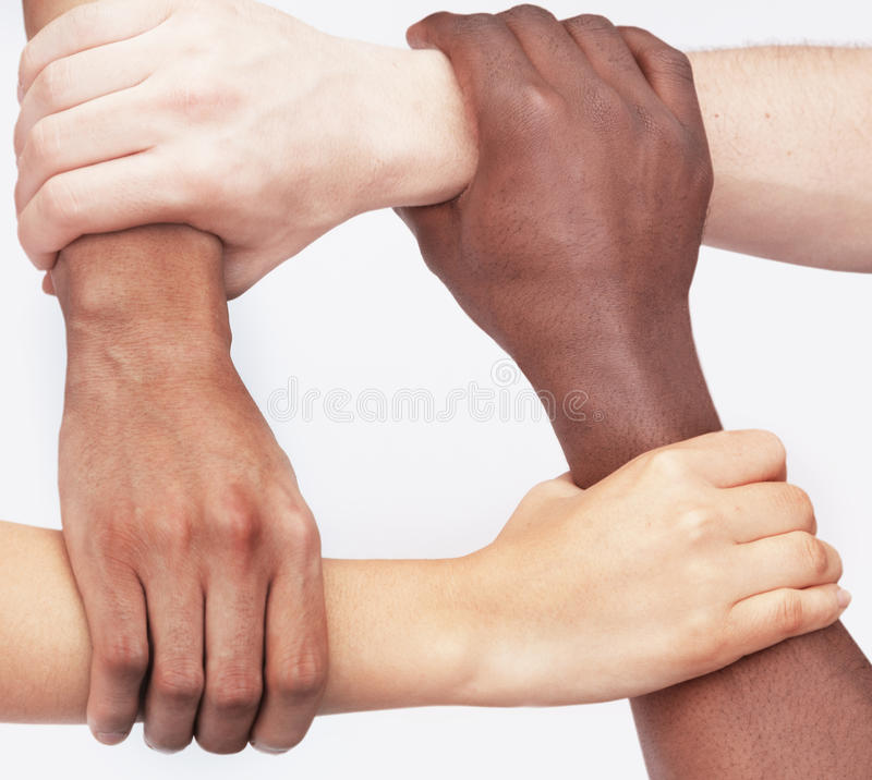 4 молодые люди держа каждые другие запястья руки в круге, конец-вверх, съемка студии стоковые фотографии rf