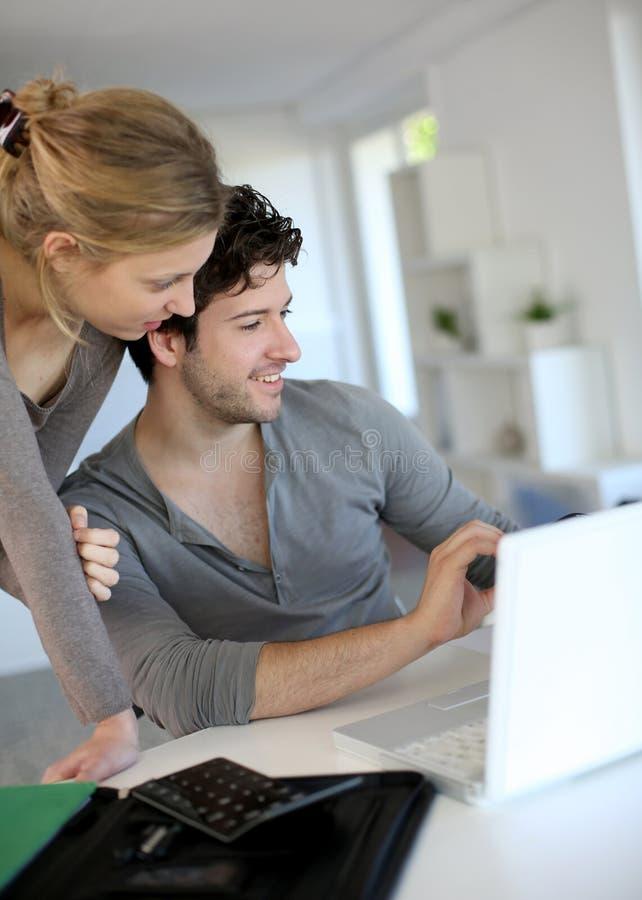 Молодые люди изучая дома на компьтер-книжке стоковые фото