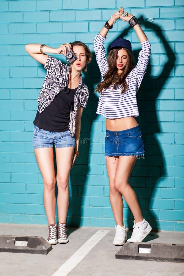 Молодые люди имея потеху перед светом - голубой кирпичной стеной стоковое фото rf