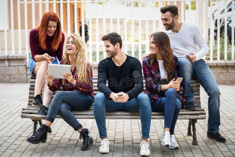 Молодые люди используя smartphone и планшеты outdoors стоковые фотографии rf