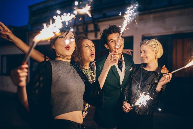 Молодые люди наслаждаясь кануном Новых Годов с фейерверками стоковое изображение