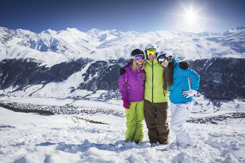 Молодые люди обнимая и представляя лыжный курорт стоковые фотографии rf