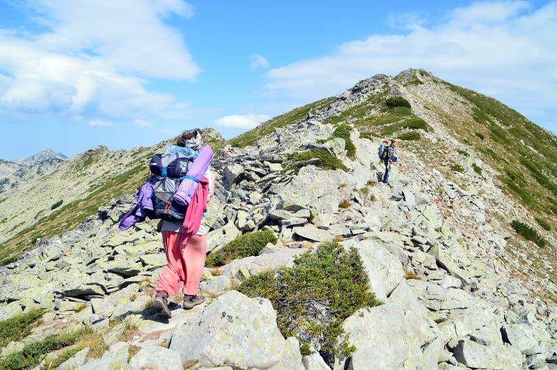 Молодые люди пешее вверх на наклоне скалистой горы стоковые фотографии rf