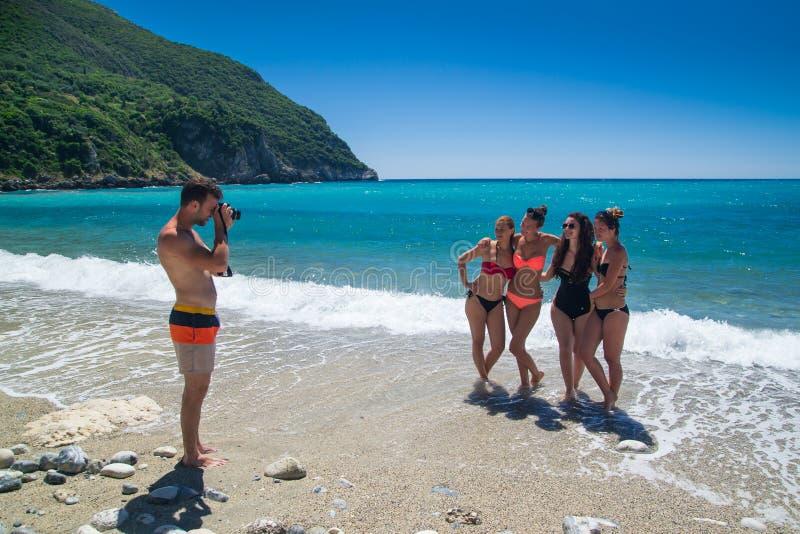 Молодые люди принимая фото на пляже стоковое фото