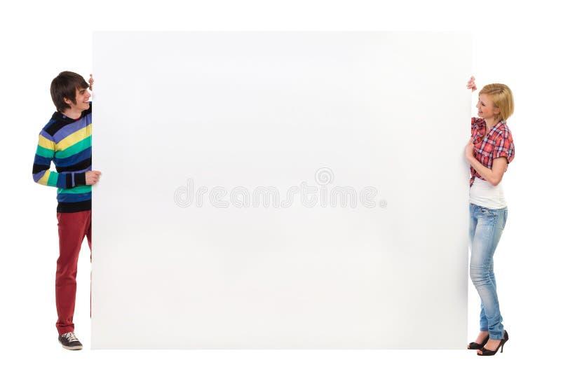 2 молодые люди проводя большой плакат стоковая фотография