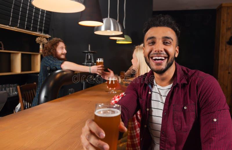 Молодые люди собирает в бар, испанское стекло владением человека провозглашать счастливый усмехаться, друзья сидя на пабе деревян стоковые изображения rf