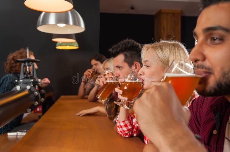 Молодые люди собирает в бар, друзей бармена сидя на пабе деревянной стойки, пиве питья стоковое фото