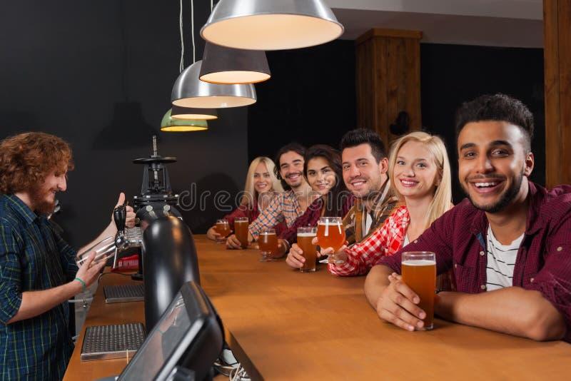 Молодые люди собирает в бар, друзей бармена сидя на пабе деревянной стойки, пиве питья стоковое изображение