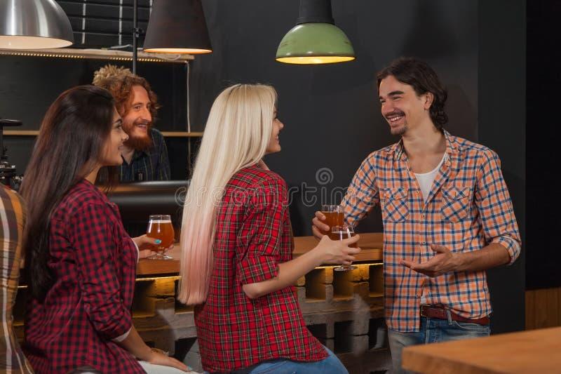 Молодые люди собирает в бар, друзей сидя на пабе деревянной стойки, пиве питья стоковые изображения rf