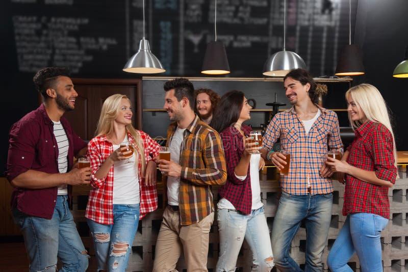 Молодые люди собирает в бар, счастливый усмехаясь паб друзей, говорить пива питья стоковое фото
