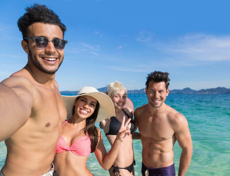 Молодые люди собирает на летние каникулы пляжа, 2 друзей пар счастливые усмехаясь принимая фото Selfie стоковая фотография