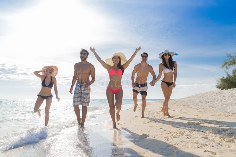 Молодые люди собирает на летние каникулы пляжа, счастливое усмехаясь взморье друзей идя стоковые изображения rf