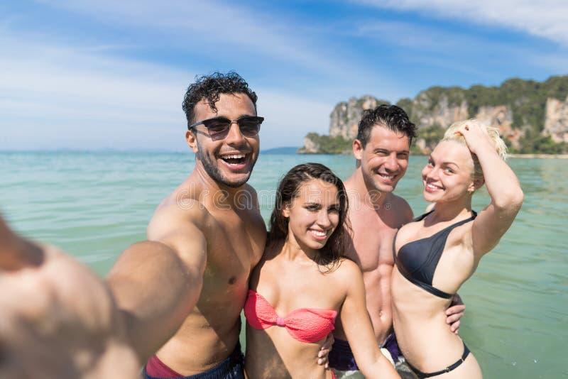 Молодые люди собирает на летние каникулы пляжа, счастливые усмехаясь друзей принимая фото Selfie в океане моря воды стоковое изображение rf