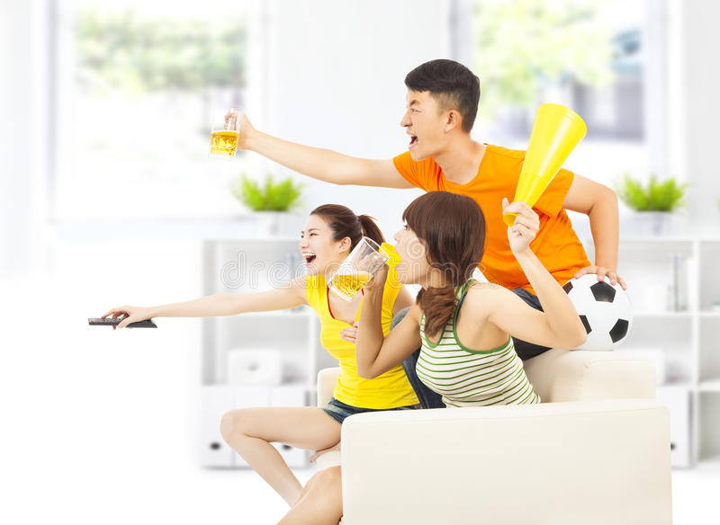 Молодые люди так возбудило к выкрикивать и пока наблюдающ футболу стоковые изображения