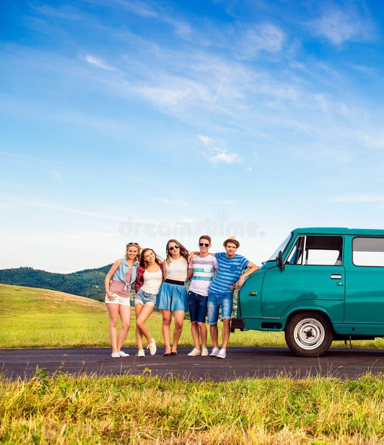Молодые frieds с campervan, зеленой природой и голубым небом стоковое фото