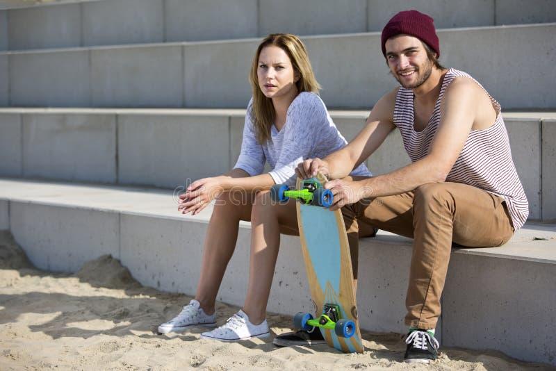 Молодые skateboarding пары на пляже стоковая фотография