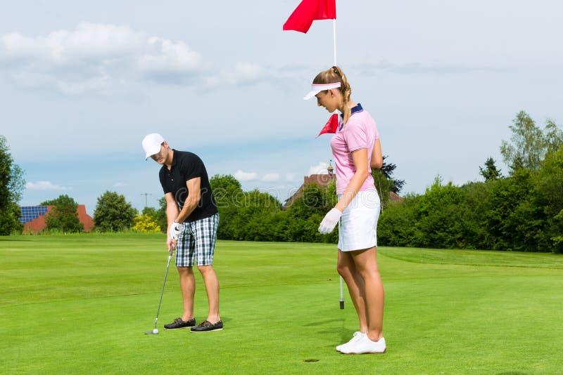 Молодые sportive пары играя гольф на курсе стоковое изображение