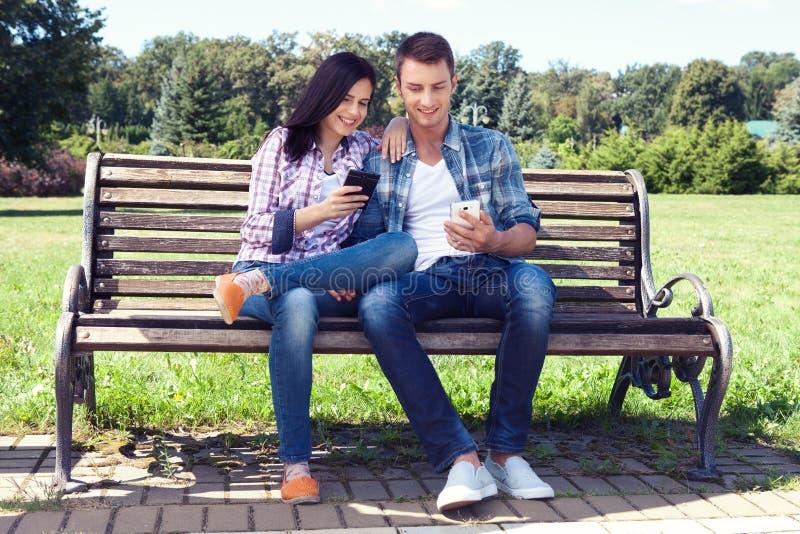 Молодыми телефон изумленный парами наблюдая умный внешний стоковое фото rf