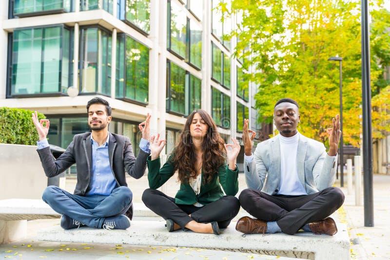 3 молодых бизнесмены делая excercises йоги во время пролома стоковые изображения rf