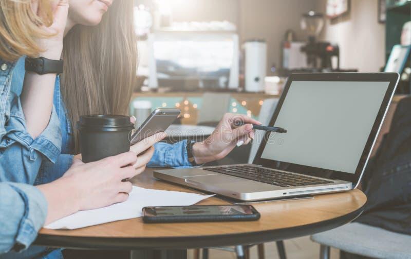2 молодых бизнес-леди сидя на таблице в кафе, выпивая кофе и говорить Первые ручка удерживания женщины и smartphone стоковые изображения