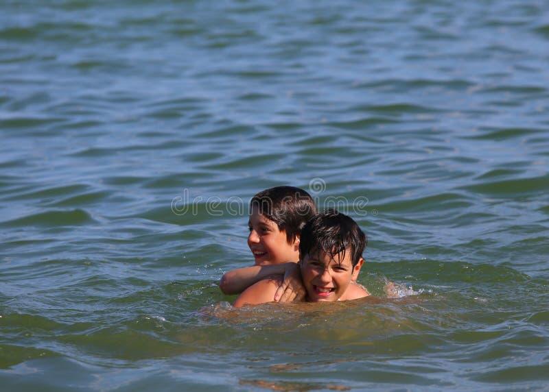 2 молодых брать играя в воде моря стоковая фотография rf