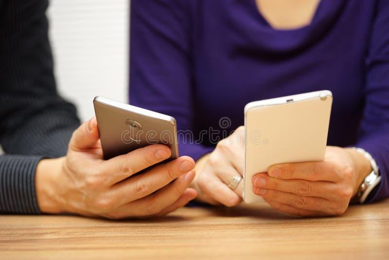 2 молодых взрослого деля музыку и файлы над передвижным умным телефоном стоковое изображение