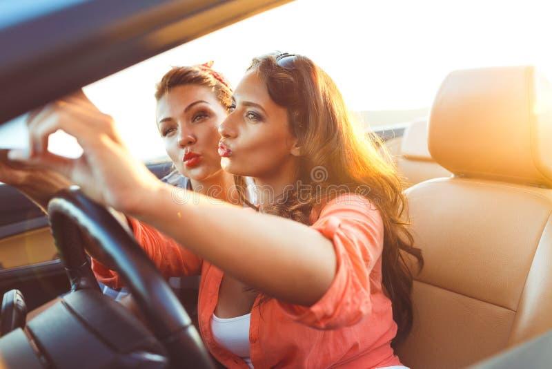 2 молодых красивых девушки делают selfie в автомобиле с откидным верхом стоковые изображения rf