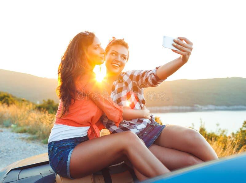 2 молодых красивых девушки делают selfie в автомобиле с откидным верхом стоковое фото rf