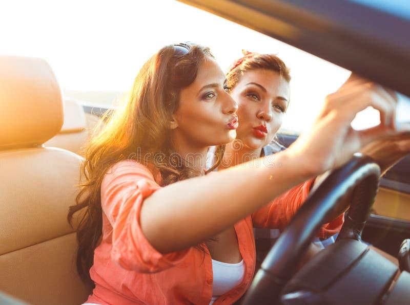2 молодых красивых девушки делают selfie в автомобиле с откидным верхом стоковые изображения