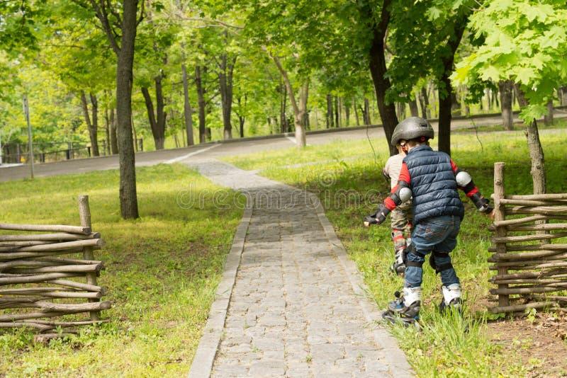 2 молодых мальчика в лезвиях ролика стоковая фотография rf