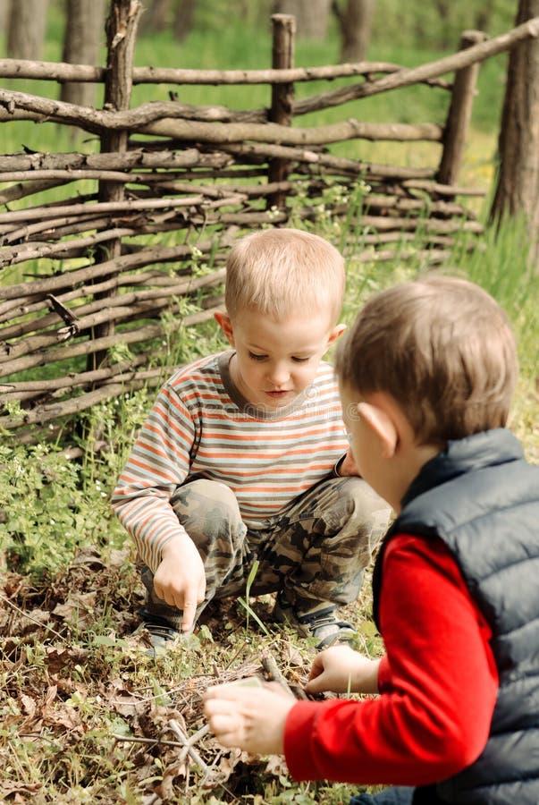 2 молодых мальчика обсуждая освещающ лагерный костер стоковое фото