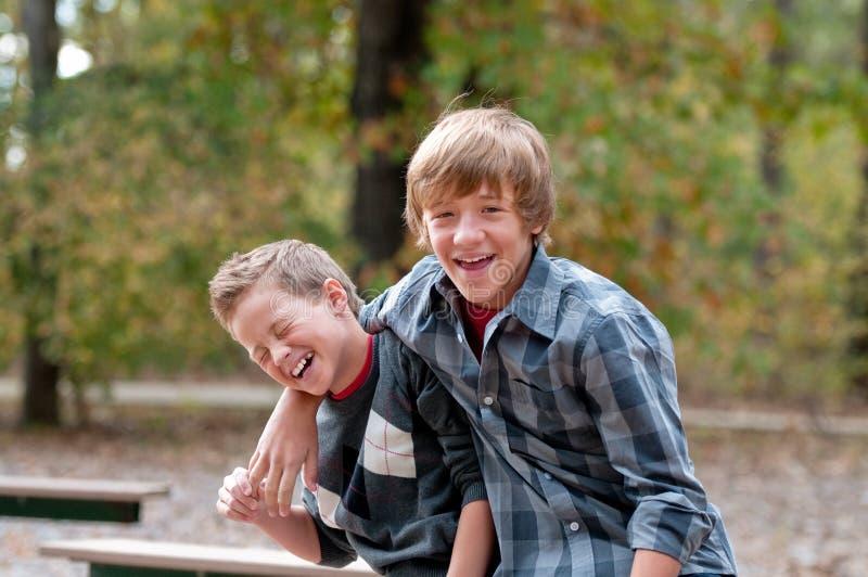 2 молодых мальчика смеясь над и хихикая стоковые фотографии rf