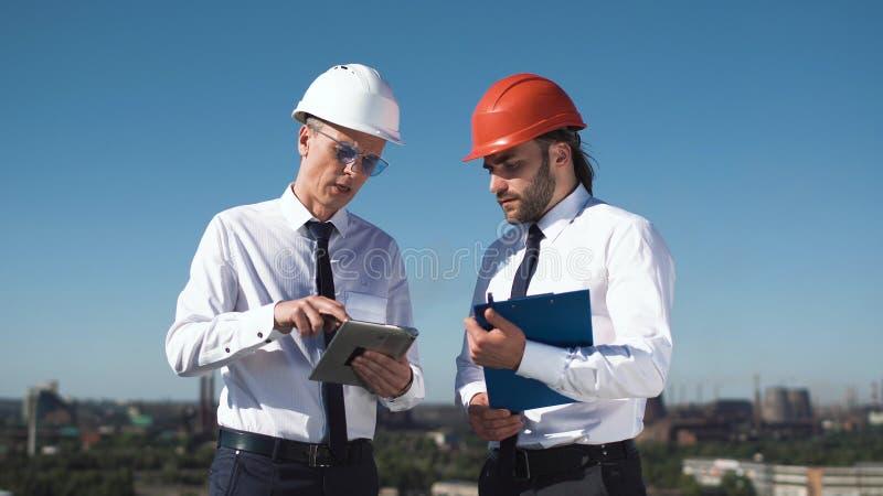 2 молодых мужских архитекторы или инженера обсуждая стоковое изображение