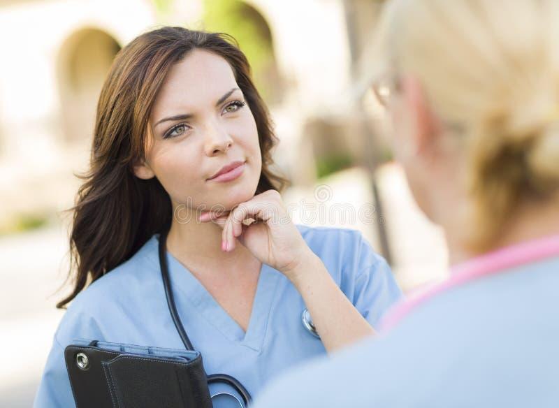 2 молодых доктора или Nuses взрослых женщины говоря снаружи стоковые изображения rf