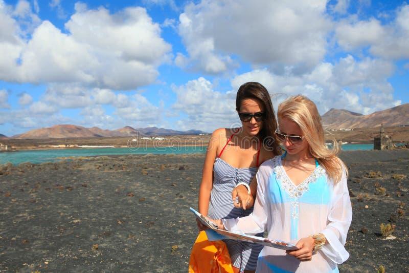 2 молодых привлекательных женщины с картой земли стоковые изображения