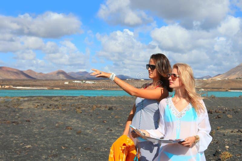 2 молодых привлекательных женщины с картой земли стоковая фотография