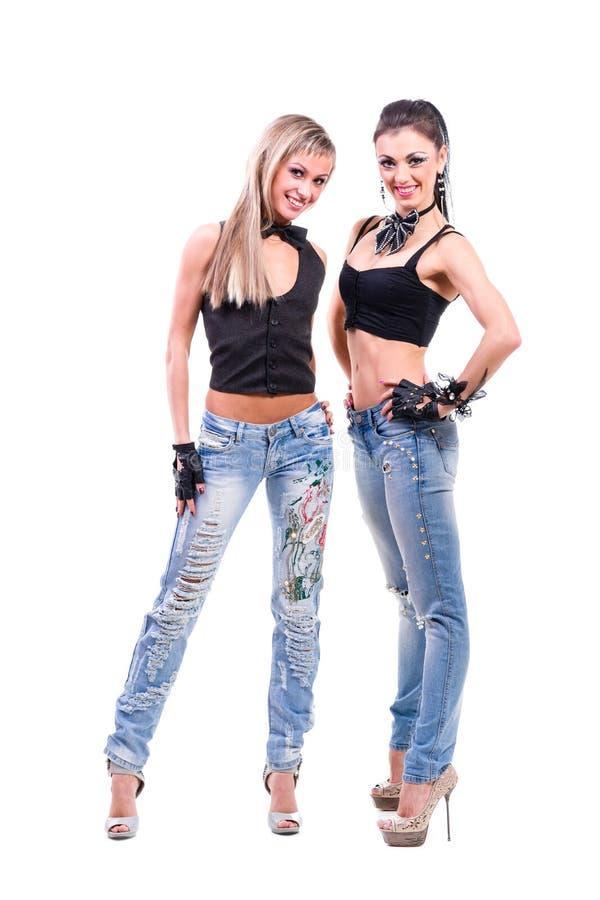 2 молодых сексуальных женщины в джинсах джинсовой ткани изолированных дальше стоковая фотография rf