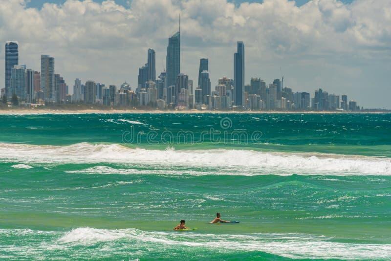 2 молодых серфера с городским пейзажем Gold Coast на предпосылке стоковые фото