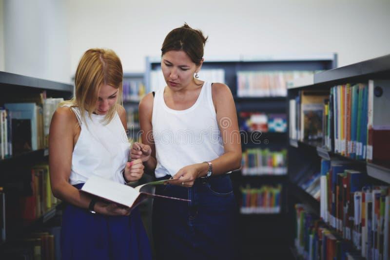 2 молодых студента подготавливая для встречи в библиотеке стоковая фотография