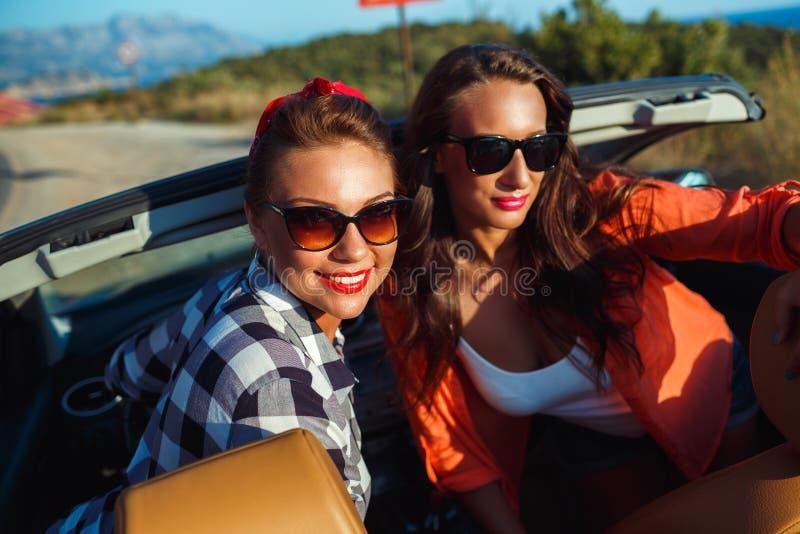 2 молодых счастливых девушки имея потеху в cabriolet outdoors стоковая фотография rf